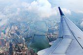 Airplane Flies Over Hong Kong. Passenger Jet Plane Flying Above Urban Scene. Hongkong Flight. Asian  poster