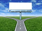 picture of paved road  - Cross roads with billboard in an outdoor display with grass and blue sky showing a fork in the road representing the concept of a strategic dilemma choosing the right direction to go when facing two equal or similar promotional options - JPG