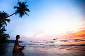 stock photo of namaskar  - Beautiful woman doing lotus yoga pose on the beach near the ocean at sunset in Thailand - JPG