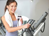 Gym woman fitness workout. Fitness girl exercising on moonwalker treadmill gym equipment. Young mixe