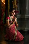 picture of sari  - Young Indian woman in traditional sari dress praying in a hindu temple - JPG