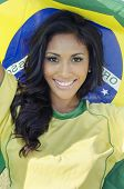 Beautiful football fan soccer in Brazilian color holding Brazil flag