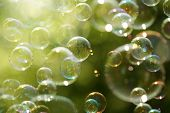 stock photo of sun flare  - Soap bubbles floating in the air as the Summer sun sets - JPG