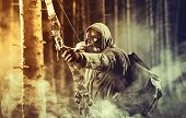 stock photo of bow arrow  - A male bow hunter wearing gas mask draws back on his bow - JPG