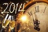 stock photo of midnight  - Glasses with champagne against fireworks and clock close to midnight 2014 - JPG