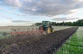 picture of plowed field  - Tractor plowing the field with modern plow - JPG
