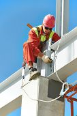 image of assemblage  - worker in uniform and safety protective equipment at metal construction frames installation and assemblage - JPG