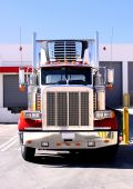 stock photo of 18 wheeler  - This is a picture of 18 wheeler refrigerated semi truck loading at a warehouse building dock - JPG