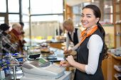stock photo of cash register  - Shopkeeper and saleswoman at cash register or checkout counter - JPG