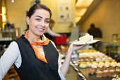 pic of confectioners  - waitress or server presenting cake in cafe - JPG