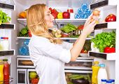 Cute female taking eggs from the fridge, attractive housewife take care about health, fresh tasty or