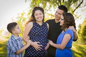 stock photo of teen pregnancy  - Happy Attractive Hispanic Family With Their Pregnant Mother Outdoors At the Park - JPG