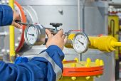 stock photo of refinery  - Operator working on barometer of oil and gas refinery - JPG