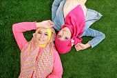 stock photo of muslimah  - Portrait of close up two beautiful happy muslim woman lying on grass - JPG