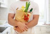 stock photo of reusable paper shopping bag  - Man holding paper bag full of groceries on the kitchen background - JPG