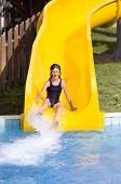 foto of toboggan  - Girl with glasses for swimming sliding on toboggan at aqua park - JPG