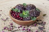 picture of sesame seed  - raw food cookies with cranberries, sesame seeds, apple and mint in a wooden bowl