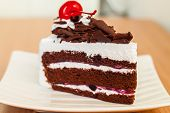 stock photo of cherry pie  - Piece of chocolate cake with cherry on the table - JPG
