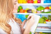 stock photo of supermarket  - Closeup photo of cute blond housewife writing list to go to supermarket - JPG