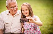 stock photo of grandfather  - Girl taking photo with mobile phone of herself and her grandfather - JPG