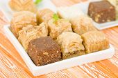 pic of baklava  - Baklava - Middle Eastern sweet pastry and nuts selection on an orange background.