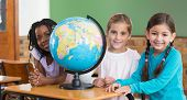 picture of pupils  - Cute pupils sitting in classroom with globe at the elementary school - JPG