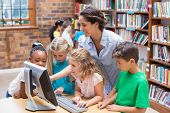 picture of pupils  - Cute pupils and teacher looking at computer in library at the elementary school - JPG