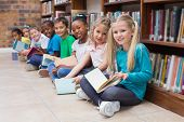 picture of pupils  - Cute pupils sitting on floor in library at the elementary school - JPG