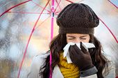 stock photo of sneezing  - Woman with cold or flu coughing and blowing her nose with a tissue under autumn rain - JPG