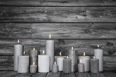 Picture of burning candles in white and grey on wooden shabby chic background.