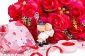 foto of fiance  - Red roses bride and fiance candle and gift box close up picture - JPG