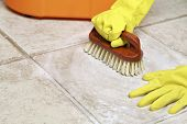 stock photo of scrubs  - hands in rubber gloves scrubbing the floor - JPG