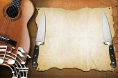 picture of bluegrass  - Acoustic guitar on wooden wall with empty parchment musical notes and two kitchen knives - JPG