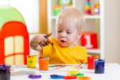picture of finger-painting  - cute kid boy painting at home or playschool - JPG
