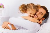 picture of hug  - Charming portrait of happy father and his small daughter in a hug on the bed in the morning - JPG