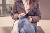 foto of ordinary woman  - Detail of a young woman working with her tablet in the city streets - JPG