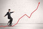 foto of unicycle  - Business parson riding unicycle on an uprising red arrow concept - JPG