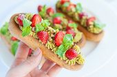 pic of eclairs  - French eclairs with whipped cream and topped with strawberries mint and pistachios on a white plate - JPG
