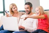 stock photo of family bonding  - Happy family of three bonding to each other and smiling while sitting on the couch and shopping online together  - JPG