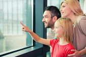 stock photo of bonding  - Happy family of three bonding to each other and smiling while looking through a window together