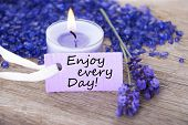 stock photo of white purple  - Purple Label With Candle Light And Lavender Blossoms With English Life Quote Enjoy Every Day Wooden Background With White Ribbon - JPG