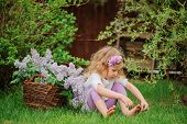 picture of headband  - horizontal portrait of cute child girl in flower headband sitting in spring garden with basket of lilacs - JPG