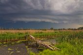 foto of terrific  - Terrific storm cyclone over the beautiful countryside river - JPG