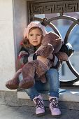picture of beret  - Little girl in a pink beret holds a toy bear - JPG
