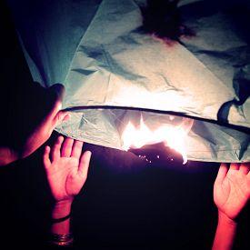 stock photo of floating  - Hands holding floating lantern  - JPG