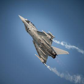 foto of fighter plane  - Jet fighter in flightclimbing in blue sky - JPG