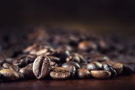 foto of coffee coffee plant  - Roasted coffee beans spilled freely on a wooden table.Coffee time