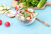 stock photo of chinese parsley  - Spring salad with radishes cucumber Chinese cabbage and red onion closeup vsteklyannoy bowl on a blue wooden background - JPG