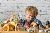 picture of dinosaur  - a little child plays with toys animals and dinosaurs - JPG