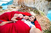 picture of sleeping bag  - Young couple lying in red sleeping bags near the sea - JPG